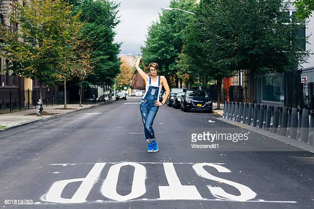 USA, New York City, Williamsburg, woman wearing jeans dungarees posing on the street