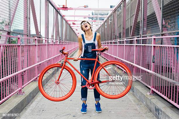 usa, new york city, williamsburg, woman with red racing cycle on williamsburg bridge - williamsburg brooklyn fotografías e imágenes de stock