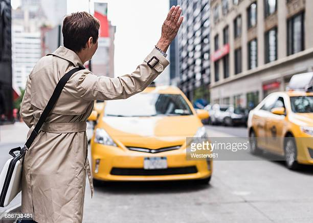 usa, new york city, woman in manhattan hailing a taxi - hail stock pictures, royalty-free photos & images
