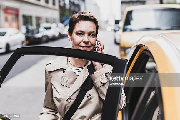 USA, New York City, woman in Manhattan on cell phone entering a taxi