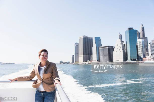 USA, New York City, woman on ferry with Manhattan skyline in background