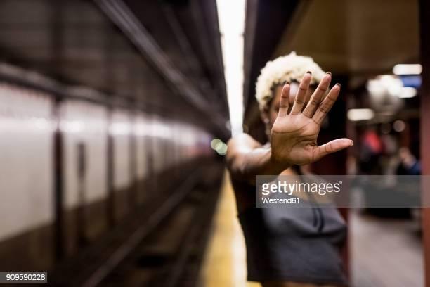 usa, new york city, woman on subway station platform showing hand palm - ストップ ストックフォトと画像