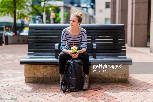 USA, New York City, woman sitting on a bench drinking a smoothie in Manhattan
