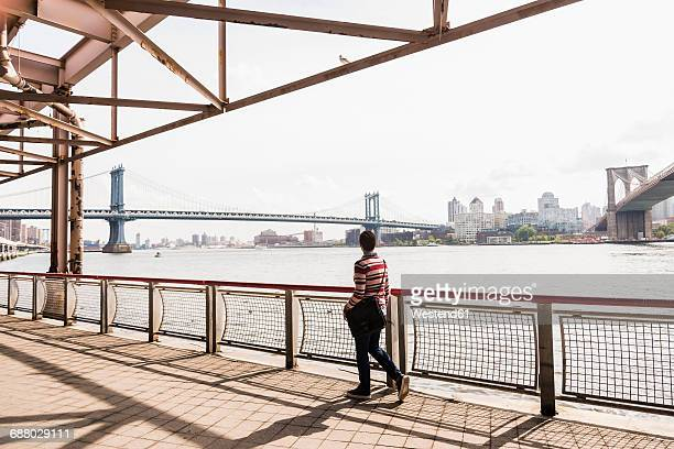 usa, new york city, woman walking at east river - shoulder bag stock pictures, royalty-free photos & images