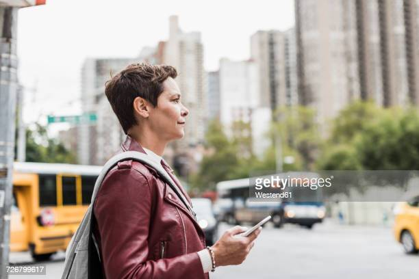 USA, New York City, woman with cell phone in the city