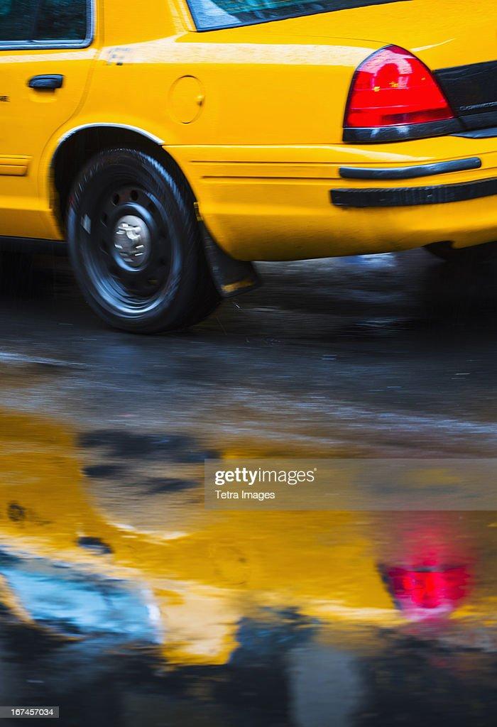USA, New York City, Yellow cab reflecting in rain puddle : Stock Photo