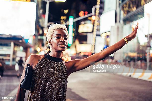 usa, new york city, young woman hailing a taxi on times square at night - hail stock pictures, royalty-free photos & images