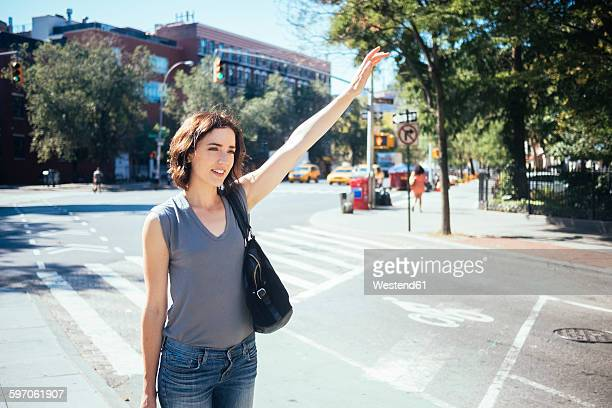 USA, New York City, young woman hailing a taxi
