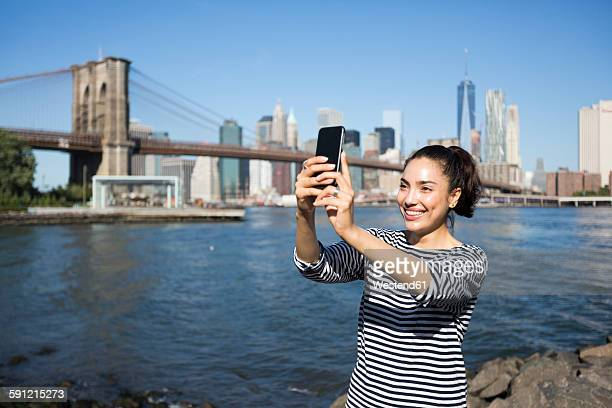 USA, New York City, young woman taking a selfie with smartphone