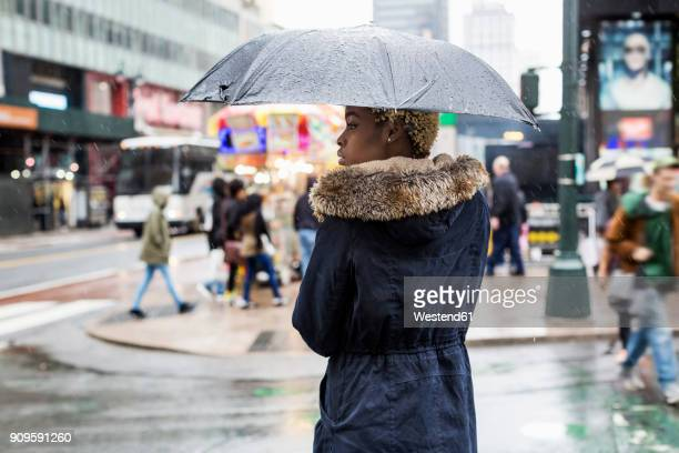 USA, New York City, young woman with umbrella on rainy day