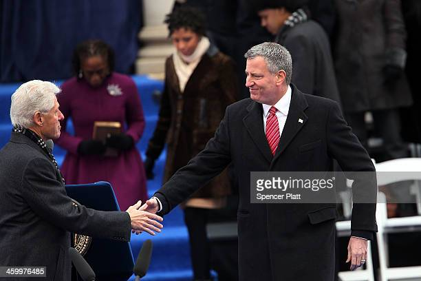 New York City's 109th Mayor Bill de Blasio shakes hands with former President Bill Clinton at City Hall before being sworn in on January 1 2014 in...