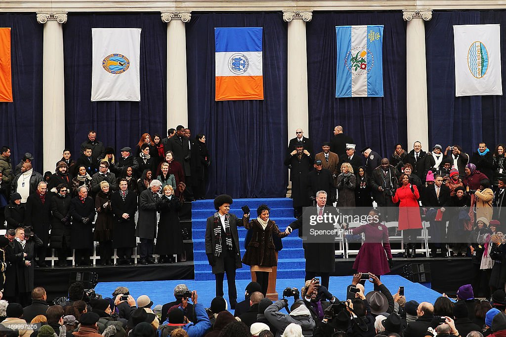 New York City's 109th Mayor Bill de Blasio stands on stage with his family at City Hall on January 1, 2014 in New York City. Mayor de Blasio was sworn in using a Bible once owned by President Franklin Delano Roosevelt. Following the 12 years of the Michael Bloomberg administration, Mayor de Blasio won on a liberal platform that emphasized the growing gulf between the rich and poor in New York City.