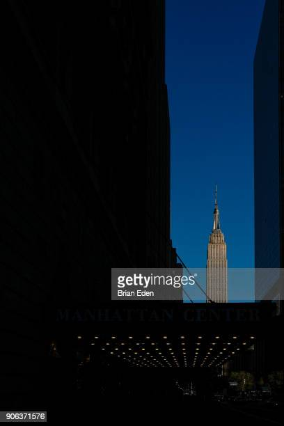 New York City's Empire State Building is seen between buildings at the end of a street in Midtown