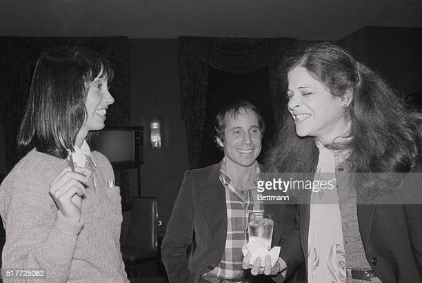 New York: Composer-singer Paul Simon listens as Gilda Radner of Saturday Night Live tells an anecdote 12/1 during celebrity party at NBC to honor...