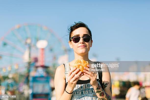 USA, New York, Coney Island, young woman eating a hamburger
