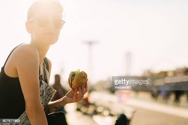 usa, new york, coney island, young woman eating a hamburger - fel verlicht stockfoto's en -beelden