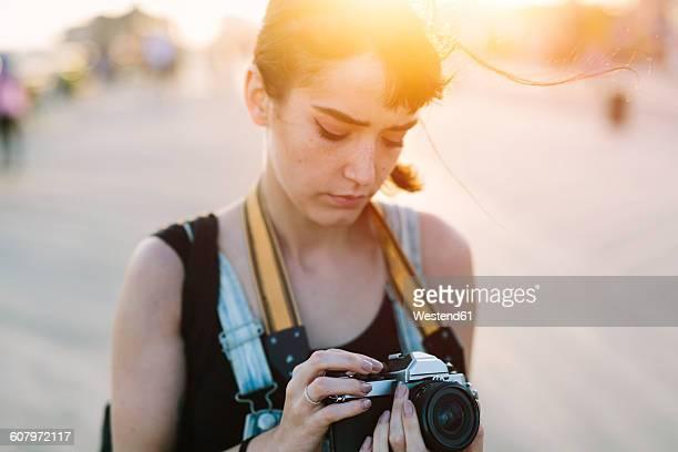USA, New York, Coney Island, young woman looking at camera at sunset