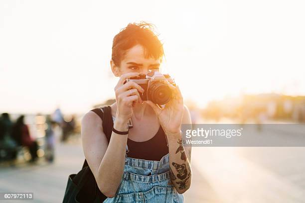 USA, New York, Coney Island, young woman taking photos at sunset