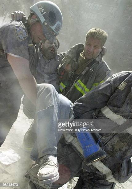 New York Daily News staff photographer David Handschuh is carried from site after his leg was shattered by falling debris while he was photographing...