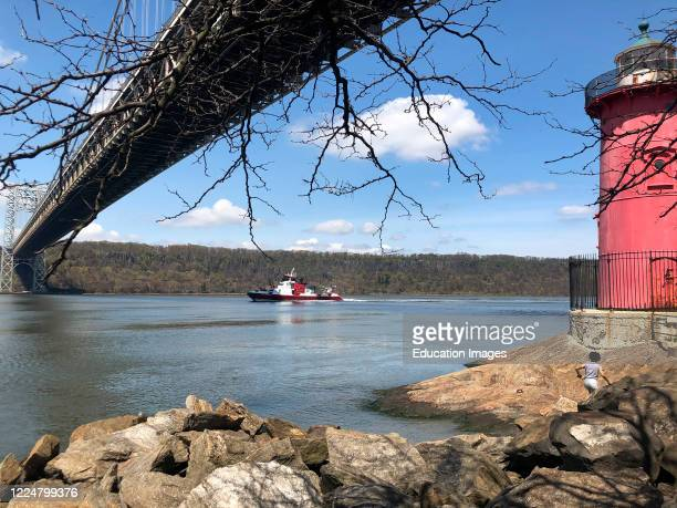 New York fire department boat underway on River Hudson under George Washington Bridge from the Little Red Lighthouse Jeffrey's Hook Light New York USA