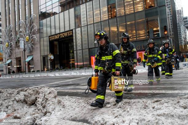New York Fire Department firefighters exit the building after responding to a small fire at Trump Tower January 8 2018 in New York City An electrical...