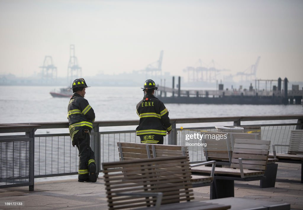 New York Fire Department (NYFD) firefighters look at the scene of a ferry accident at Pier 11 in New York, U.S., on Wednesday, Jan. 9, 2013. Seastreak Wall Street commuter ferry crashed into a pier near Lower Manhattan's financial district during the morning rush hour, injuring dozens, including two critically, police said. Photographer: Scott Eells/Bloomberg via Getty Images