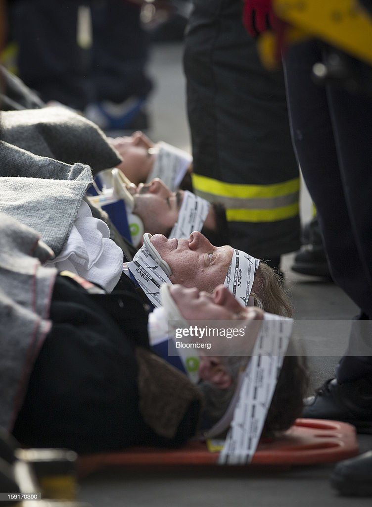 New York Fire Department (NYFD) firefighters prepare to take away injured ferry commuters on stretchers in New York, U.S., on Wednesday, Jan. 9, 2013. A Seastreak commuter ferry crashed into a pier near Lower Manhattan's financial district during the morning rush hour, injuring dozens, including two critically, police said. Photographer: Scott Eells/Bloomberg via Getty Images