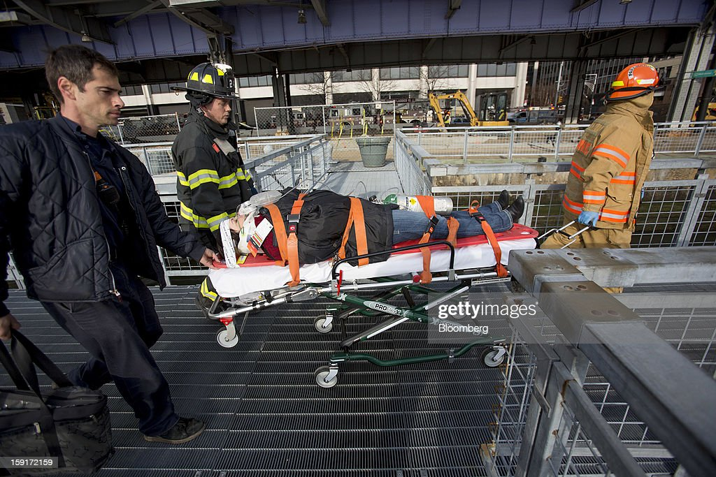 New York Fire Department (NYFD) firefighters take away an injured ferry commuter on a stretcher in New York, U.S., on Wednesday, Jan. 9, 2013. A Seastreak Wall Street commuter ferry crashed into a pier near Lower Manhattan's financial district during the morning rush hour, injuring dozens, including two critically, police said. Photographer: Scott Eells/Bloomberg via Getty Images