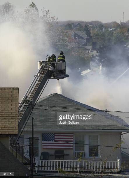 New York firefighters spray water on a burning house that was hit by American Airlines flight 587 November 12, 2001 in Rockaway Beach, New York City....