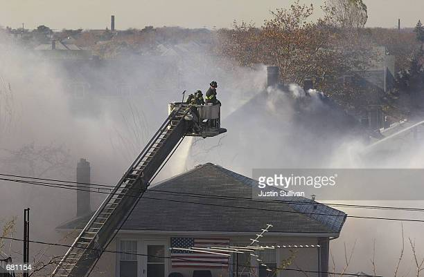 New York firefighters spray water on a burning house that was hit by American Airlines flight 587 as it crashed November 12, 2001 in Rockaway Beach,...