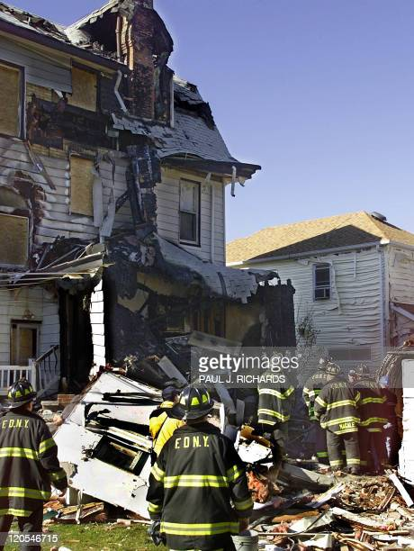New York firemen work in the backyard of a house in the Belle Harbor section of Queens New York 14 November 2001 which was damaged in the 12 November...