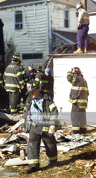 New York firemen work in the yard of a house in the Belle Harbor section of Queens New York 14 November 2001 which was damaged when an engine from...