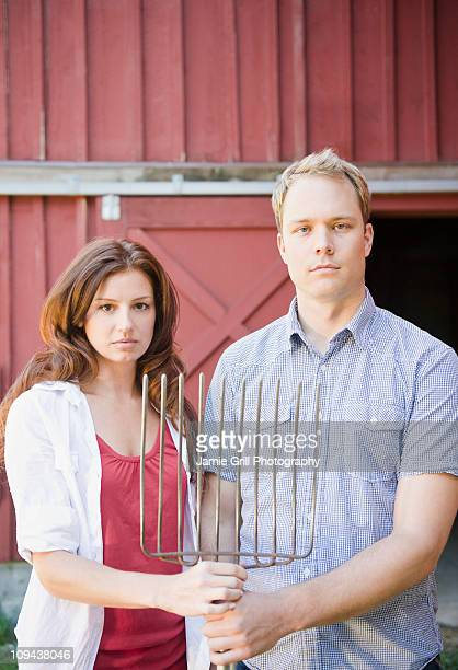 USA, New York, Flanders, Portrait of mid adult couple with pitchfork