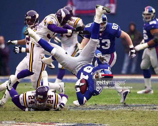 New York Giants' Amani Toomer is upended but hangs onto the ball after receiving pass in play against the Minnesota Vikings in the NFC Championship...