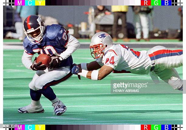 New York Giants' Chris Calloway is tackled by the New England Patriots' Maurice Douglas in the first quarter of their game at Giants Stadium in East...