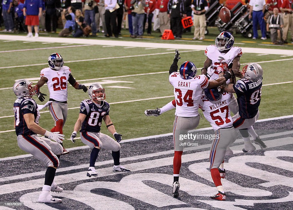 New York Giants defenders knock down the football from Aaron Hernandez #81 of the New England Patriots in the fourth quarter during the game against the New England Patriots during Super Bowl XLVI at Lucas Oil Stadium on February 5, 2012 in Indianapolis, Indiana.