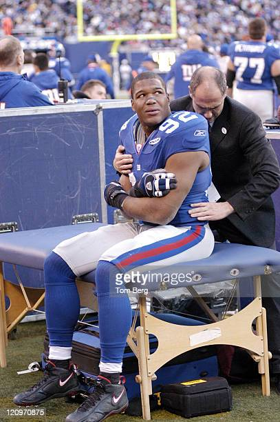 New York Giants Defensive End Michael Strahan being looked at by New York Giants doctor after a play he came off the field in pain during...