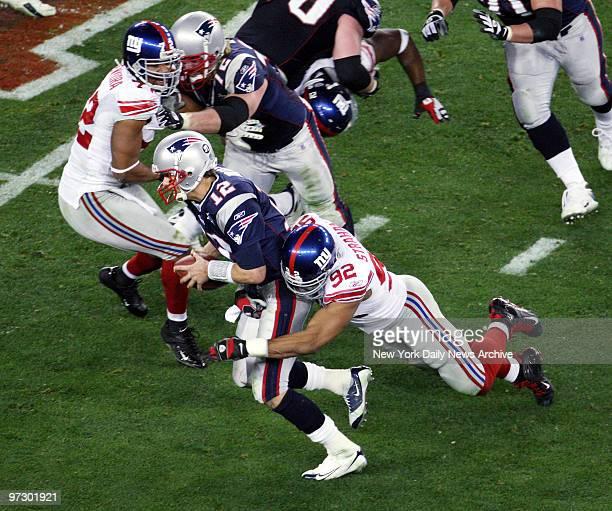 New York Giants' defensive end Michael Strahan sacks New England Patriots' quarterback Tom Brady in the third quarter of Super Bowl XLII at the...