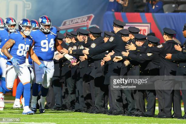 New York Giants defensive tackle Dalvin Tomlinson and teammates high five New York City Police Officers prior to the National Football League game...