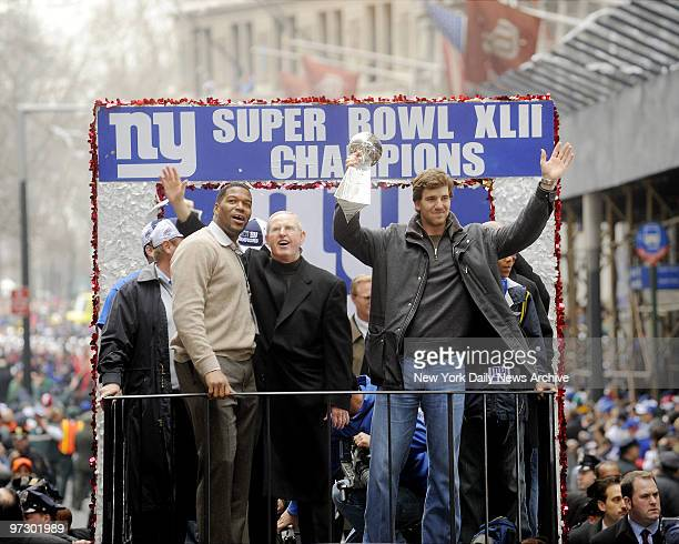 New York Giants' Eli Manning hold his team's Super Bowl trophy as he rides a float alongside head coach Tom Coughlin and Michael Strahan during the...