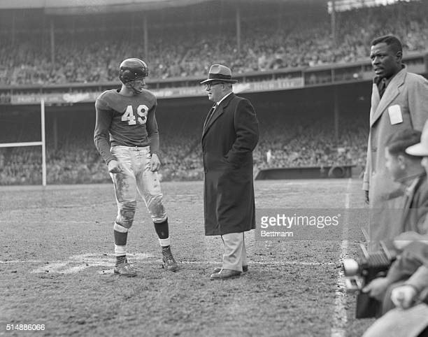 New York Giant's football coach Steve Owen on the sidelines talking to player Tom Landry