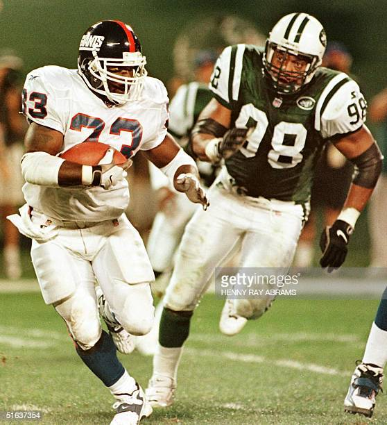 New York Giants' Gary Brown runs from New York Jets' Anthony Pleasant during the second quarter of their preseason exhibition game 20 August at...