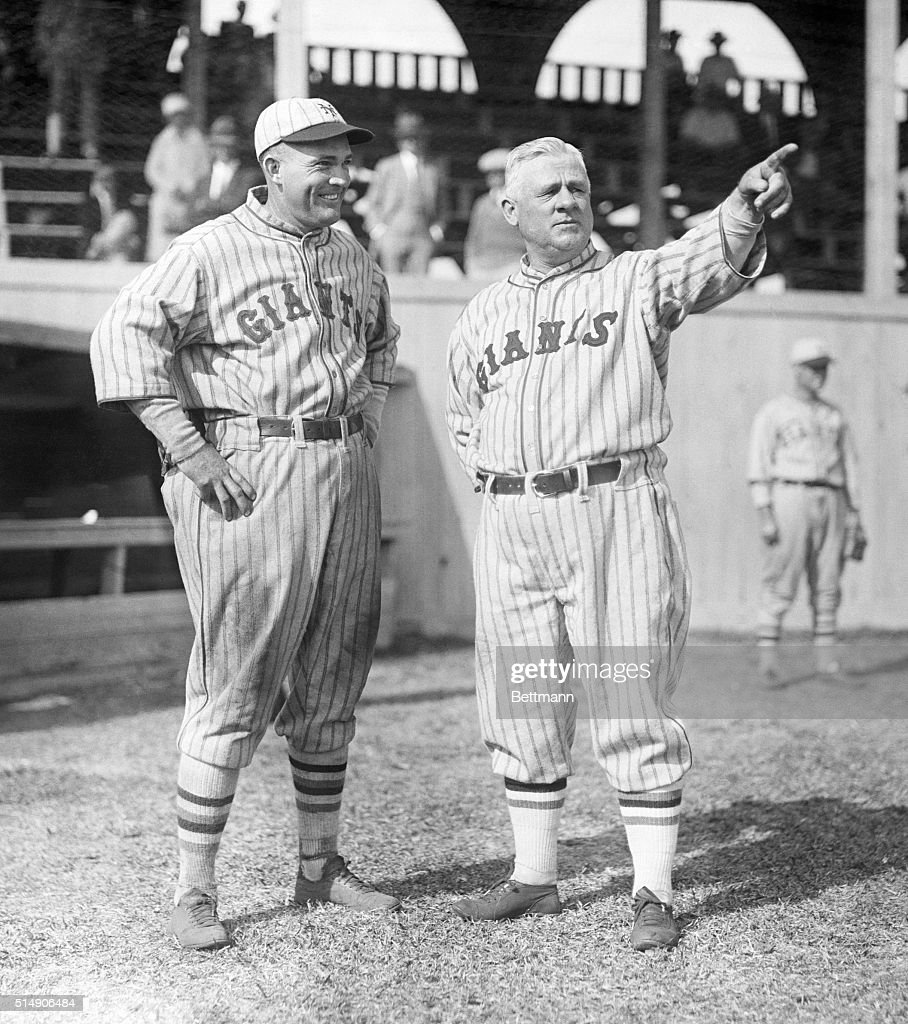New York Giants' John J. McGraw (R) directs teammate Rogers Hornsby's attention outfield as the two stand in uniform near the dugout.