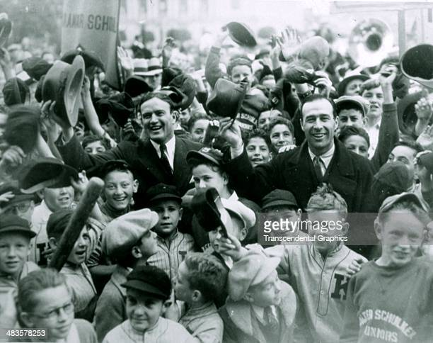 New York Giants Lefty O'Doul, right in suit, and the Washington Senators' Joe Cronin return home after the baseball season to a rousing welcome from...