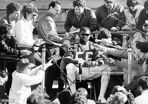 New York Giants' linebacker Lawrence Taylor is besieged by microphones at a news conference.