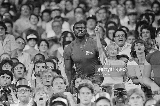 New York Giant's linebacker Lawrence Taylor stands amongst the spectators at Giant stadium to get a better view of his team in action during the...