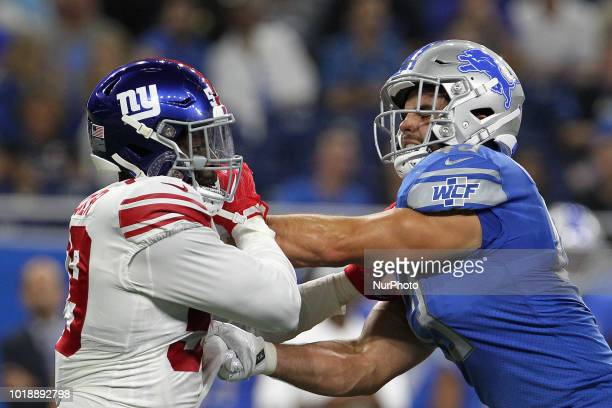 New York Giants linebacker Lorenzo Carter holds the line against Detroit Lions fullback Nick Bellore during the first half of an NFL football game...