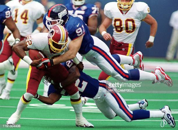 New York Giants linebacker Ryan Phillips and cornerback Phillipi Sparks team up to tackle Washington Redskins wide receiver Michael Westbrook after a...
