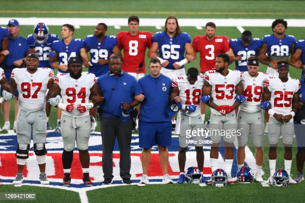 New York Giants lock arms in a pregame moment of silence prior to the start of the Blue and White scrimmage at MetLife Stadium on August 28, 2020 in...