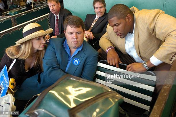 ELMONT NY New York Giants' Michael Strahan left joins his wife Jean right and friend Mark Kent as they watch the replay of the Smarty Jones loss in...